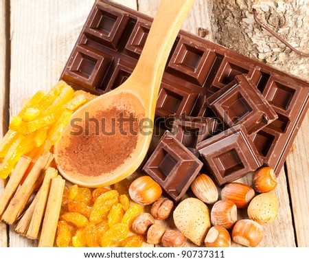 Chocolate bar and chunks with cocoa powder, dried fruit and assorted nuts over a wooden table