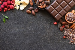 Chocolate bar, crushed pieces of dark chocolate and cocoa beans, cocoa butter, pieces of dried strawberries culinary background, top view