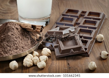 chocolate bar with cocoa powder, cinnamon, nuts and milk on wood table