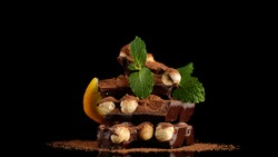 chocolate bar with nuts, decorate sliced orange and mint leaf. chocolate with nuts. confectionery concept