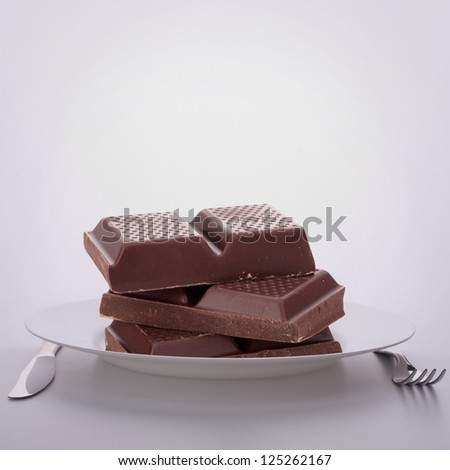 Chocolate bars stack on plate. Unhealthy eating concept.