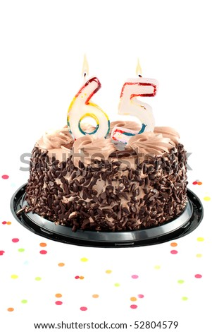 Chocolate birthday cake surrounded by confetti with lit candle for a seventy fifth birthday or anniversary celebration