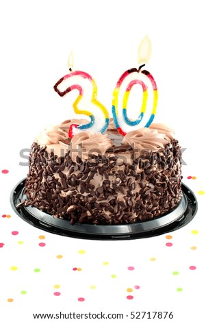 Chocolate birthday cake surrounded by confetti with lit candle for a thirtieth birthday or anniversary celebration - stock photo