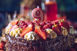 Chocolate birthday cake with candle. 9th birthday cake.