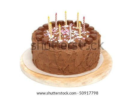 Chocolate birthday cake with candles on wooden cutting board over white background
