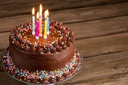 Chocolate birthday cake with colorful sprinkles and candles over wooden background.