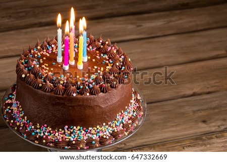 Chocolate Birthday Cake With Colorful Sprinkles And Candles Over Wooden Background 647332669