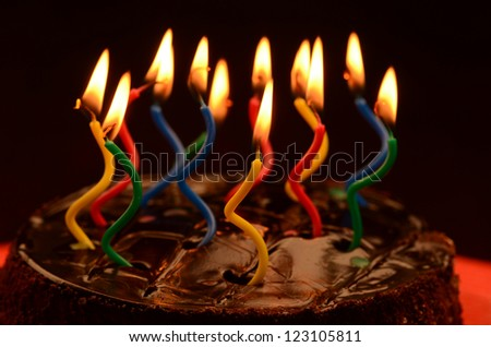 Chocolate birthday cake with lit novelty candles.