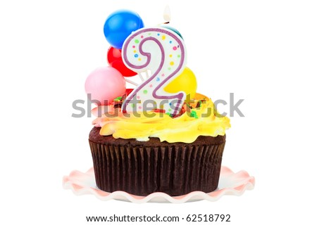 Chocolate birthday cake with number  two candle and plastic balloons. Isolated on a white background.