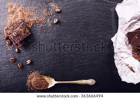 Chocolate. Black chocolate. A few cubes of black chocolate. Chocolate slabs spilled from grated chocolate powder. Coffee beans.