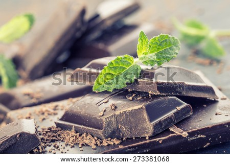 Chocolate. Black chocolate. A few cubes of black chocolate with mint leaves. Chocolate slabs spilled from grated chockolate powder.
