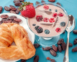 chocolate breakfast smoothie, with berries and bread, on a lightblue background, it has a spoon on the side and cacao beans.