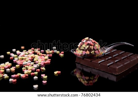 chocolate - brigadier on a spoon, with nuggets heart-shaped, colored, on black with reflexion