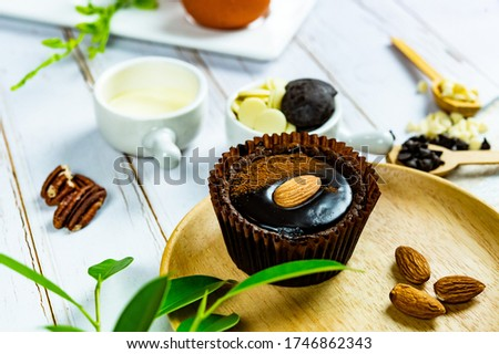 Chocolate Brownie Cake in Paper Cups Decorated with components for making cakes placed on wooden floors