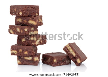 Chocolate brownie cake stack with loose chunks to one side, over white background.
