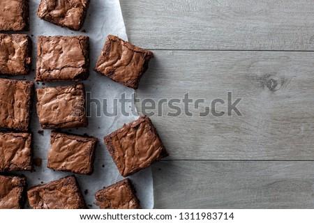 Chocolate brownie on paper on dark grey base top view flat lay looking down #1311983714