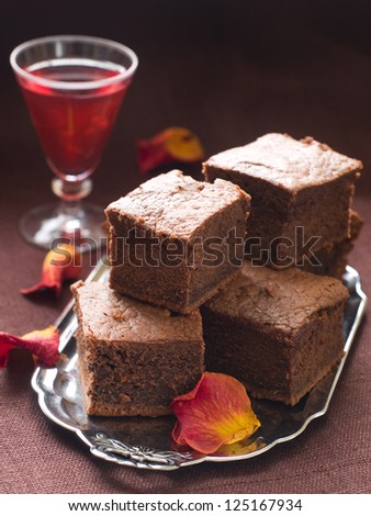 Chocolate brownie on plate with rose petal, selective focus