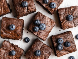 Chocolate brownie squares with chewy and moist texture, melting chocolate and fresh blueberries. Delicious homemade fudge (or brownie cake) pieces. Close up view. Top view food. Flat layout.