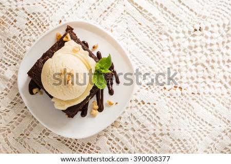 Chocolate brownie with vanilla ice cream, nuts and mint, served om white plate, copy space