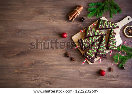 Chocolate Brownies in shape of Christmas Trees with green icing and festive sprinkles on wooden table, top view, copy space. Sweet homemade Christmas or winter holidays pastry food concept.