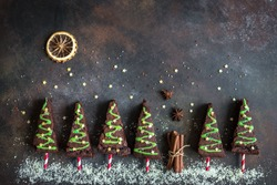 Chocolate Brownies in shape of Christmas Trees with green icing and festive sprinkles, top view, copy space. Sweet Christmas or winter holidays pastry food concept.