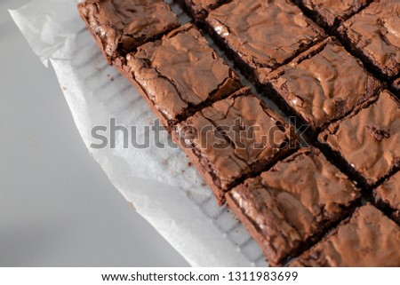 Chocolate brownies on a paper sheet on a metal rack on a grey worktop at an angle #1311983699