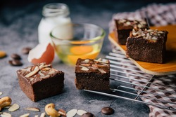 Chocolate brownies squares on a cooling tray, and on a cutting board , a brown kitchen towel, with egg, milk, and a ingredient on a classic table. Freshly baked brownies. Best fudgy brownies cakes.