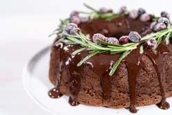 Chocolate bundt cake with chocolate frosting decorated with fresh cranberries and rosemary covered in a white sugar.