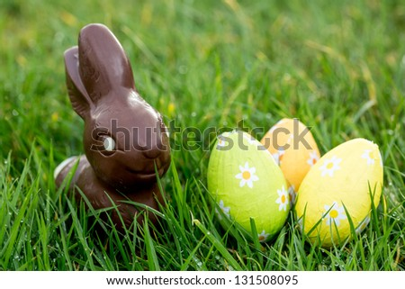 Chocolate bunny in the grass with three wrapped easter eggs