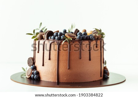 Chocolate cake decorated with blueberries, cookies and chocolates on a white background. Flat lay of the brown birthday cake