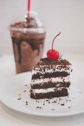Chocolate cake decorated with cherries on white dish and cocoa smoothies.