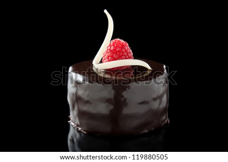 chocolate cake decorated with raspberries isolated on black