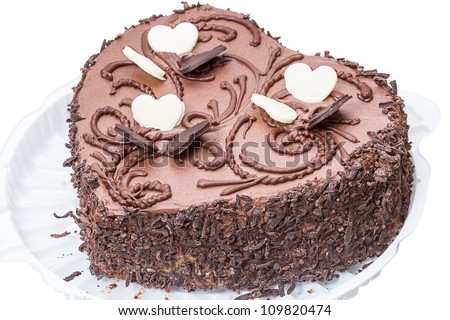 Chocolate cake in the shape of a heart on a plastic plate. Isolated on a white background.