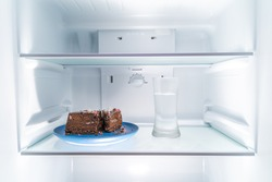 Chocolate cake on a blue plate and a glass of water placed in a clean refridgerator, diet or food concept