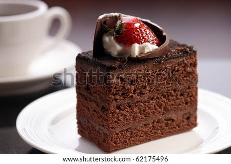 chocolate cake on the white plate with a cup of coffee