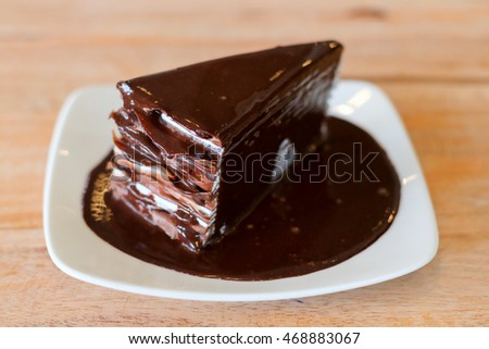 Chocolate cake on white dish and wood table in coffee shop. #468883067