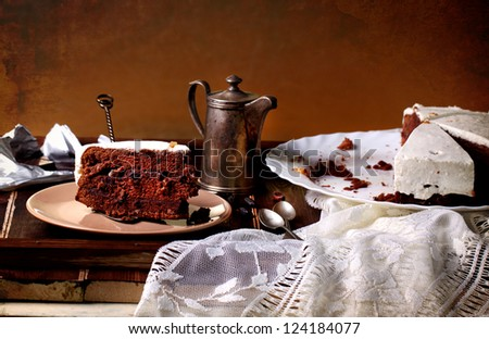 Chocolate cake on wooden table with old silver coffeepot