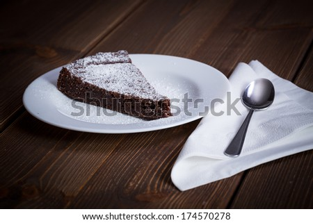 Chocolate Cake Slice on white dish and wooden background