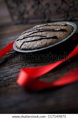 Chocolate cake. Souffle with red ribbon on wood.