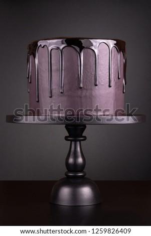 Chocolate cake with black glaze on a black background.