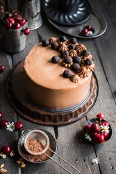 chocolate cake with cherries and nuts is decorated with mini-cakes, chocolate cheese cream and nuts on a wooden dark background. Fresh cherry and chamomile flowers