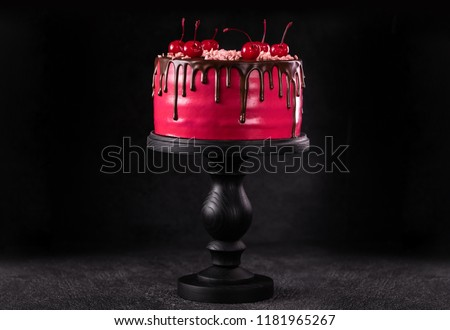 Chocolate cake with cherries on a wooden stand on a black background