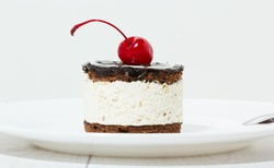 Chocolate cake with cherry on the top icing on the plate