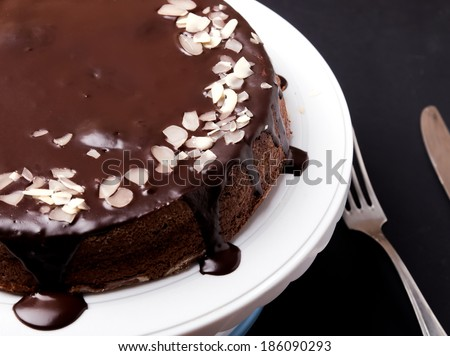 Chocolate cake with chocolate frosting on black background