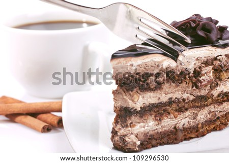 chocolate-cake with cream,  cup with coffee and cinnamon on white background