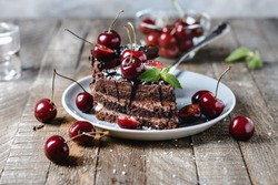 Chocolate cake with fresh cherries on a plate.
