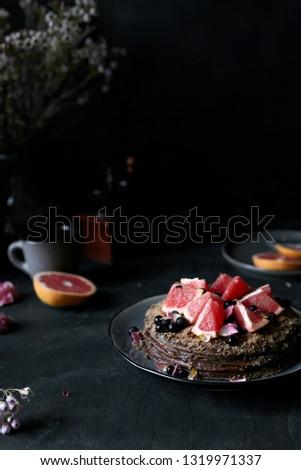 chocolate cake with grapefruits in dark atmosphere, rustic atmosphere #1319971337