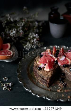 chocolate cake with grapefruits in dark atmosphere, rustic atmosphere #1319971349