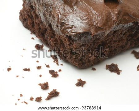 Chocolate cake with icing on white that is crumbling apart