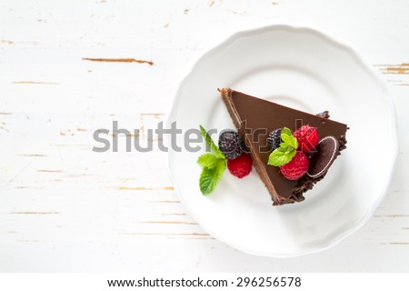 Chocolate cake with raspberry, blackberry, mint, white plate, white wood background, top view